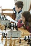 Jong kind die een beweging met een paard maken tijdens een schaaktoernooien op een school, met verscheidene andere concurrenten o Stock Foto's