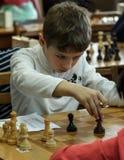 Jong kind die een beweging met een paard maken tijdens een schaaktoernooien op een school, met verscheidene andere concurrenten o Royalty-vrije Stock Foto