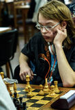 Jong kind die een beweging met een paard maken tijdens een schaaktoernooien op een school, met verscheidene andere concurrenten o Royalty-vrije Stock Afbeeldingen
