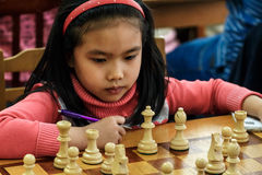 Jong kind die een beweging met een paard maken tijdens een schaaktoernooien op een school, met verscheidene andere concurrenten o Royalty-vrije Stock Afbeelding