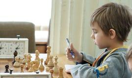 Jong kind die een beweging met een paard maken tijdens een schaaktoernooien op een school, met verscheidene andere concurrenten o Royalty-vrije Stock Foto's