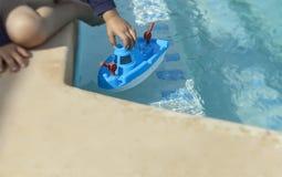 Jong kind het spelen met stuk speelgoed boot stock afbeelding