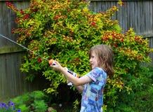 Jong kind het spelen met waterkanon Stock Fotografie