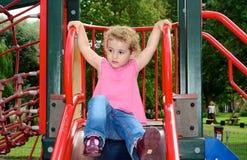 Jong kind het spelen op een dia bij de speelplaats. Stock Foto's