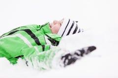 Jong kind ontspannen die op de verse sneeuw liggen Royalty-vrije Stock Foto's
