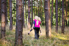 Jong kindjongen die zijn zustervervoer per kangoeroewagen in openlucht in het bos geven Royalty-vrije Stock Afbeeldingen