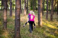 Jong kindjongen die zijn zustervervoer per kangoeroewagen in openlucht in het bos geven Stock Foto
