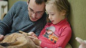 Jong kindmeisje met vader speelspel op mobiele phonein donkere ruimte, stock video