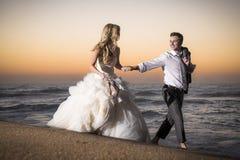 Jong knap bruids paar die langs strand bij zonsopgang lopen Stock Foto's