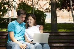 Jong knap paar die notitieboekje in het openbare park gebruiken stock foto's