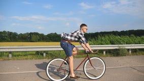 Jong knap personenvervoer bij uitstekende fiets in de landweg Het sportieve kerel cirkelen bij het spoor Het mannelijke fietser b Stock Afbeeldingen