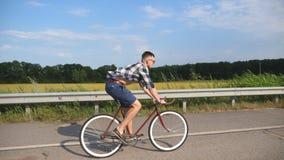 Jong knap personenvervoer bij uitstekende fiets in de landweg Het sportieve kerel cirkelen bij het spoor Het mannelijke fietser b Royalty-vrije Stock Foto