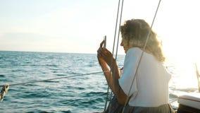 Jong krullend meisje die op een jachtzitting op het dek en het gebruik smartphone varen stock video