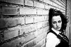 Jong krullend meisje op muur Stock Afbeelding