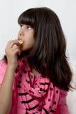 Jong Latijns Meisje die Spaanders eten Stock Foto