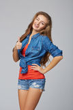 Jong leuk glimlachend emotioneel meisje die u duim, over grijs opgeven Royalty-vrije Stock Foto's