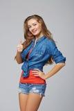 Jong leuk glimlachend emotioneel meisje die u duim, over grijs opgeven Stock Fotografie