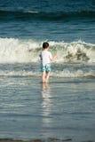 Jong leuk weinig jongen die bij de kust spelen die de branding op een zandig strand in de zomerzonneschijn tegenkomen Stock Foto's