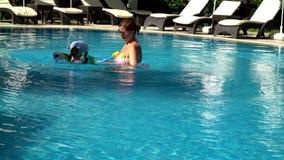 Jong mamma die met haar weinig dochter in een zwembad zwemmen stock video