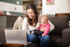 Jong mamma die thuis met haar baby werken Stock Afbeelding