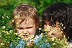 Jong mamma met haar zoon onder de de zomermadeliefjes Stock Afbeeldingen