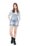 Jong maniermeisje in jeansoverall geïsoleerd stellen Stock Afbeeldingen