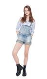Jong maniermeisje in jeansoverall geïsoleerd stellen Royalty-vrije Stock Foto