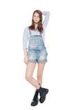 Jong maniermeisje in jeansoverall geïsoleerd stellen Stock Afbeelding