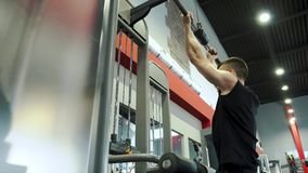 Jong mannelijk bodybuilder opleidingswapen en achterspieren in uitoefenaar in de gymnastiek stock videobeelden