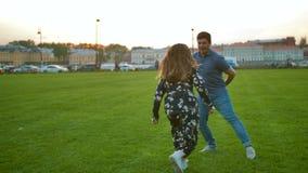 Jong mannelijk en vrouwelijk spel in een park en het hebben van pret stock footage
