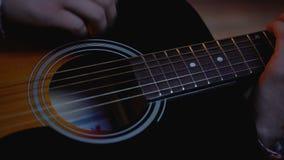 Jong mannetje die akoestische gitaar, droom over musicuscarrière spelen, close-up stock videobeelden