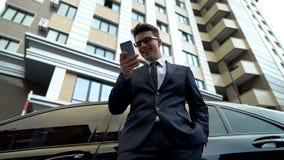 Jong mannetje die in kostuum goed nieuws op smartphone, ontvangen financiering voor opstarten lezen stock afbeelding