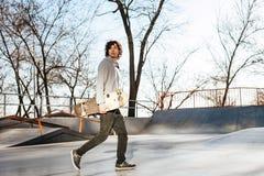 Jong mannetje die skateboarder met longboard op grijs stellen stock afbeelding