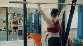 Jong meisje, atletisch, in de gymnastiek Zij doet de barbelloefening stock videobeelden