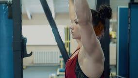 Jong meisje, atletisch, in de gymnastiek Zij doet de barbelloefening Close-up stock footage