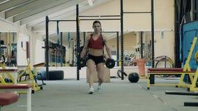 Jong meisje, atletisch, in de gymnastiek Zij gaat langs de zaal over, buigend met domoren stock footage