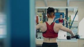 Jong meisje, atletisch, in de gymnastiek Zij heft domoren op, opleidt de spieren van haar schouders stock videobeelden