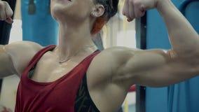 Jong meisje, atletisch, in de gymnastiek Zij toont haar spierhulp aan, dan, onderzoekt de camera Close-up stock videobeelden