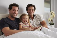 Jong meisje in bed met haar mannelijke ouders, die aan camera kijken royalty-vrije stock foto's
