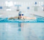 Jong meisje in beschermende brillen die vlinderslagstijl zwemmen Stock Afbeeldingen