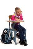 Jong Meisje bij bureau in school op wit Stock Afbeeldingen