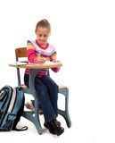 Jong Meisje bij bureau in school op wit Stock Foto