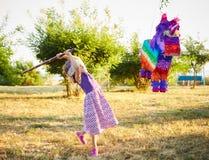 Jong meisje bij een openluchtpartij die een pinata raken Stock Afbeeldingen
