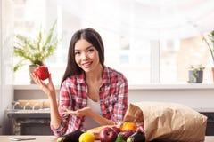 Jong meisje bij keuken gezonde levensstijl status die op lijst die groene paprika tonen aan camera het glimlachen leunen stock foto