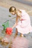 Jong meisje bij strand met netto en emmer stock afbeeldingen