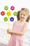 Jong meisje bij strand met stuk speelgoed windmolen het glimlachen stock foto's