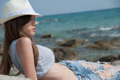 Jong meisje borrels en gewassenbovenkant dragen en hoed die buiten stellen Stock Foto's