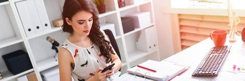 Jong meisje in bureau het typen tekst in telefoon stock foto