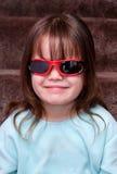 Jong meisje dat binnen koel met zonnebril op kijkt stock foto