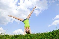 Jong meisje dat cartwheel doet royalty-vrije stock fotografie